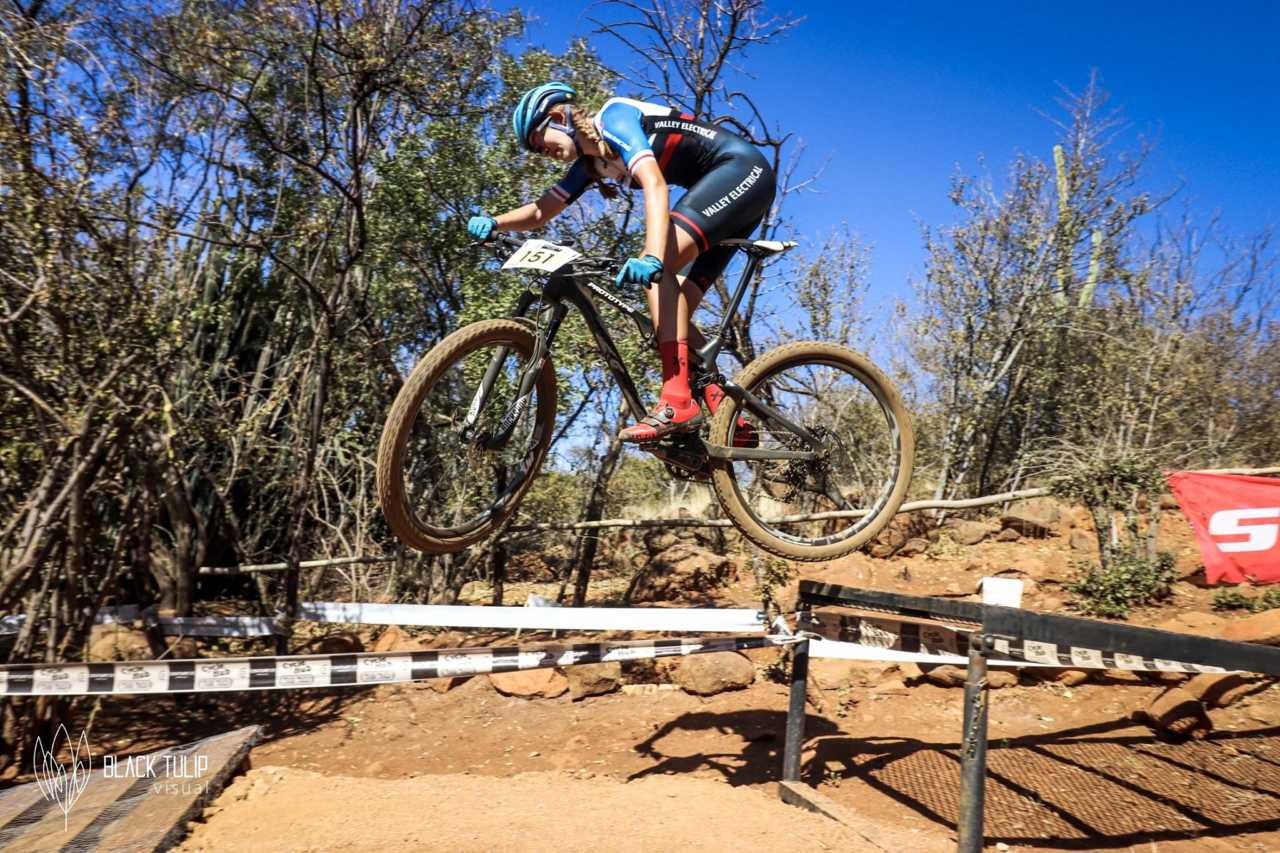 Tiffany Keep from Titan Racing jumps here prototype bike over the gap at Thaba Trails during the South African Cross Country Mountain bike championships in July 2019.
