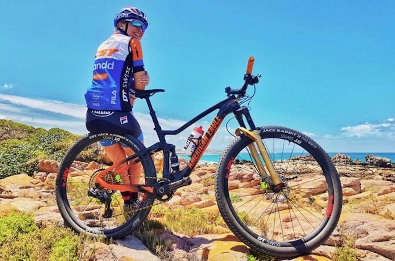 mariske strauss of the cst sandd bafang team on the beach in south africa with her new mountain bike.