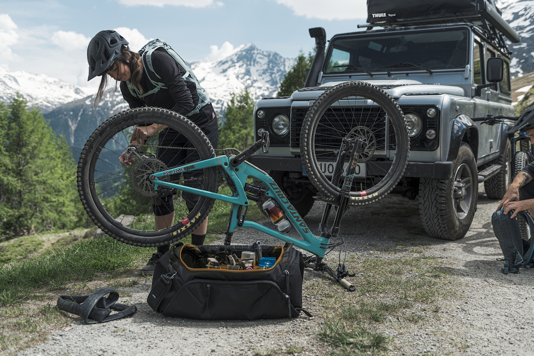 A mountain biker working on his santa cruz mega tower with the New thule roundtrip duffel bag