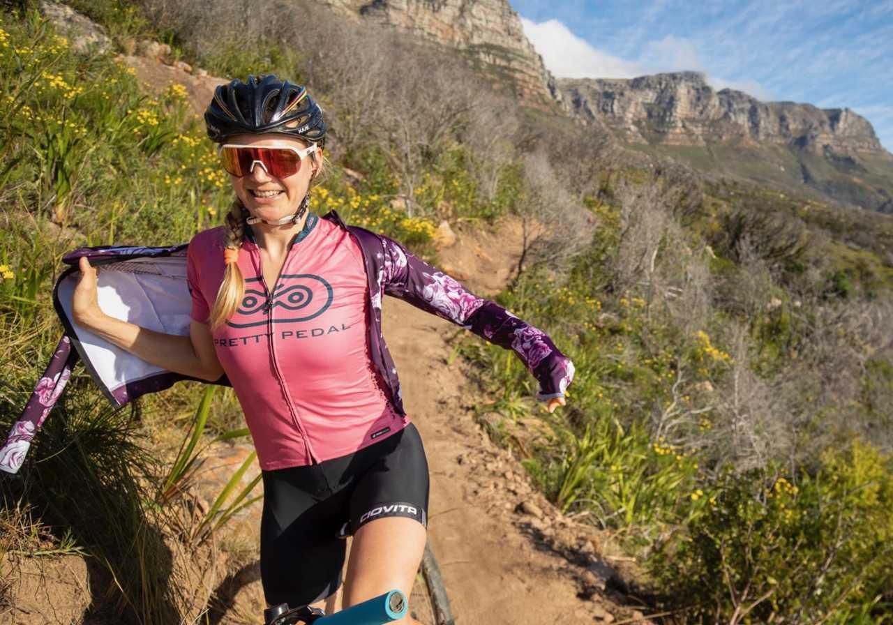 Kate Slegrova of Pretty Pedal in action on her mountain bike with the Ciovita Ladies Botanica Lava Jacket riding on the Twelve Apostle mountain range near Cape town South Africa